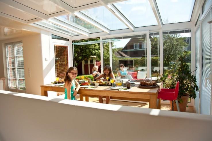 Sonnen- und lichtdurchfluteter Wintergartenraum mit perfekter offener Küche, großem Esstisch sowie Loungesofa.